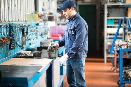 protected plant: Worker securing a metal plate in a vise Stock Photo