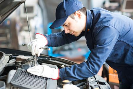 mecanico automotriz: Retrato de un mecánico de automóviles en el trabajo sobre un coche en su garaje