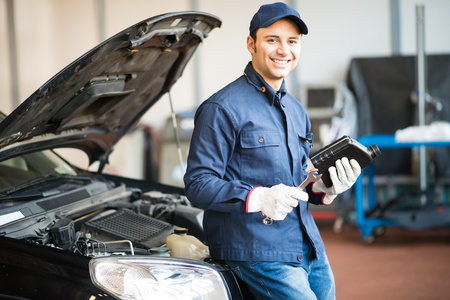 oil change: Portrait of an auto mechanic holding a jug of motor oil Stock Photo