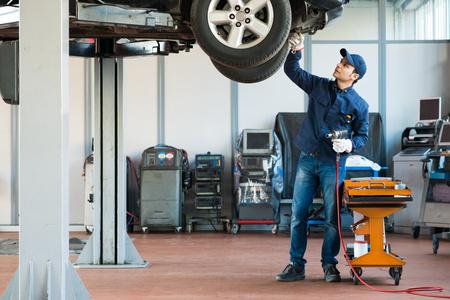 herramientas de mec�nica: Retrato de un mec�nico en el trabajo en su garaje