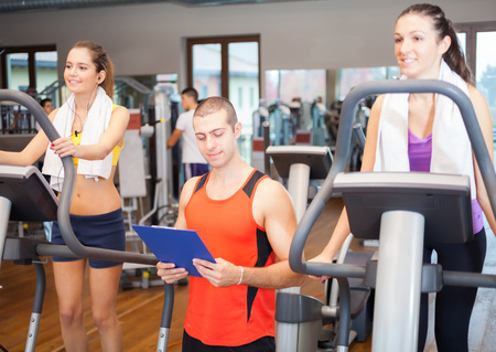 Women working out in a gym under the guide of a personal trainer photo