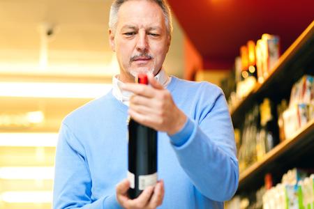 Man in a supermarket choosing a wine bottle photo