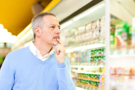 Portrait of a man searching for a product in a supermarket photo