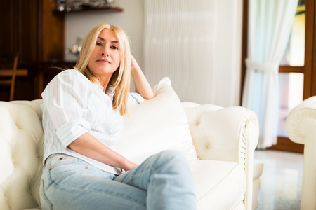 luxury apartment: Portrait of a smiling woman relaxing on the couch in her home