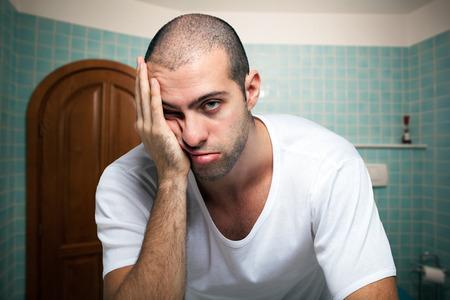 agotado: Retrato de un hombre cansado que mira en el espejo en el baño