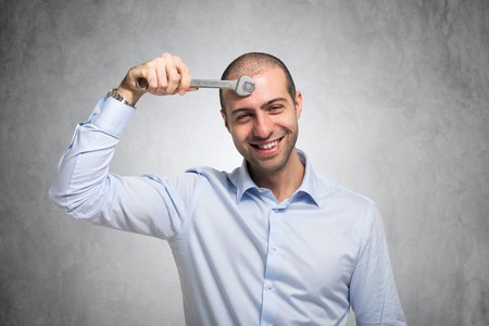 Smiling man using a wrench to adjust his mind Stockfoto