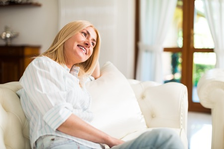 rich people: Portrait of a smiling woman relaxing on the couch in her home
