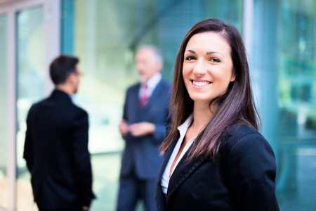 businesswoman: Smiling businesswoman in front of a group of business people Stock Photo