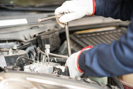 車のエンジンに取り組んでいる自動車整備士のクローズ アップ