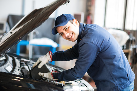 Portrait of an auto mechanic putting oil in a car engine Stockfoto