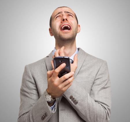 molesto: Retrato de un hombre desesperado que sostiene su teléfono móvil Foto de archivo