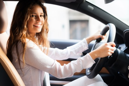new motor vehicles: Young woman driving her car
