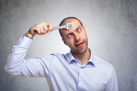 unintelligent: Funny man using a wrench to fix his brain Stock Photo