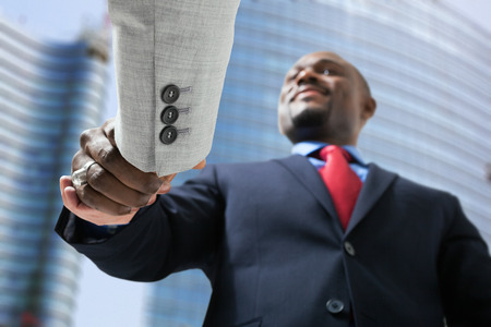 african american handshake: Portrait of a businessmen shaking hands in a business environment