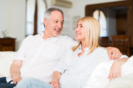 old sofa: Portrait of an happy mature couple talking in their home. Shallow depth of field, focus on the man