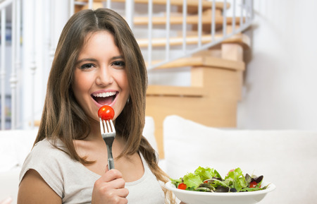 fork: Woman eating healthy food Stock Photo