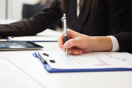 take a note: Close-up of a woman taking notes during a meeting Stock Photo
