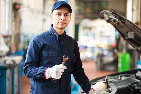 mecanico: Mecánico que sostiene una llave en su garaje