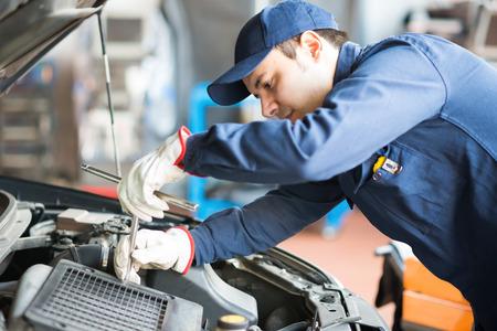 Ritratto di un meccanico di auto al lavoro su una macchina nel suo garage