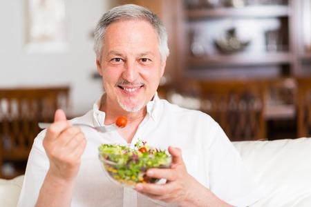 Portrait eines Mannes, isst einen Salat in seiner Wohnung