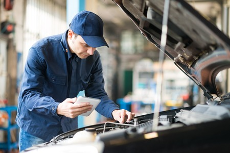 mecanico: Retrato de un mec�nico con una tableta en su garaje Foto de archivo