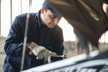 air cleaner: Retrato de un mecánico de automóviles en el trabajo sobre un coche en su garaje