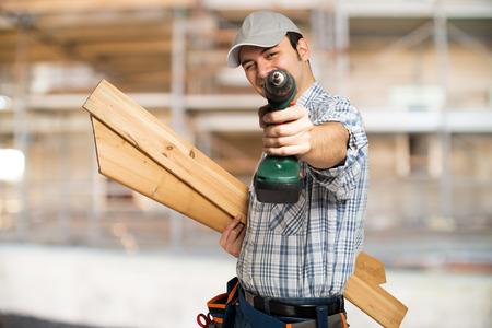Portret van een timmerman houten planken en een boor in een bouwplaats