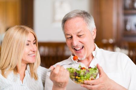 Coppia giovane che mangia un'insalata in salotto. Profondità di campo, concentrarsi su l'uomo