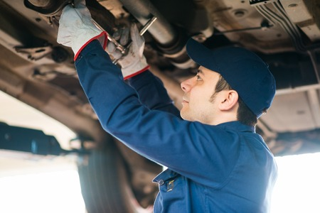 impact wrench: Portrait of a mechanic repairing a car in his garage