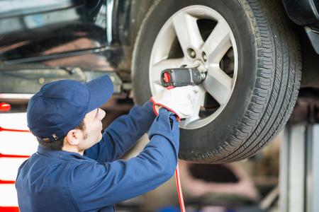 garage mechanic: Portrait of a mechanic replacing a wheel