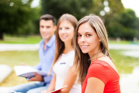 master degree: Outdoor portrait of three students studying in a park