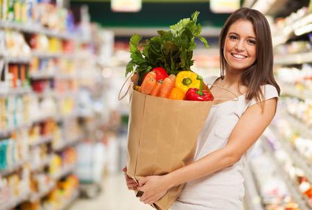 Gesunde positive glückliche Frau mit einem Papier-Einkaufstasche voll von Obst und Gemüse