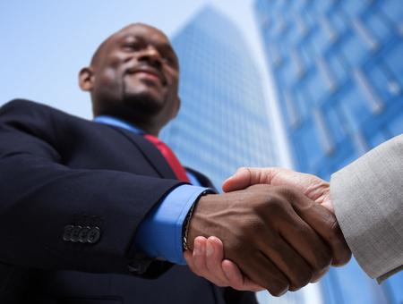 Portrait von Geschäftsleuten Händeschütteln in einer Geschäftsumgebung