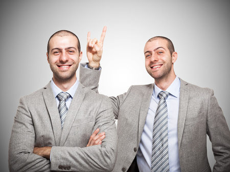 multiple personality: Funny businessman making the horns sign to himself Stock Photo