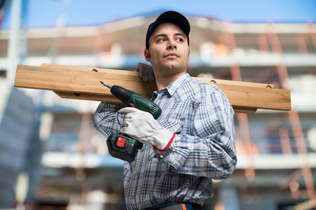 woodworker: Portrait of a carpenter wood planks and a drill in a construction site