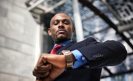 hombres negros: Apuesto hombre de negocios que buscan a su reloj