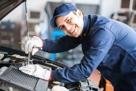 mecanico automotriz: Retrato de un sonriente fijaci�n de un motor de un coche en su garaje Foto de archivo