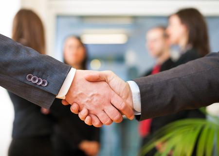apreton de manos: Gente de negocios dándose la mano en una oficina Foto de archivo