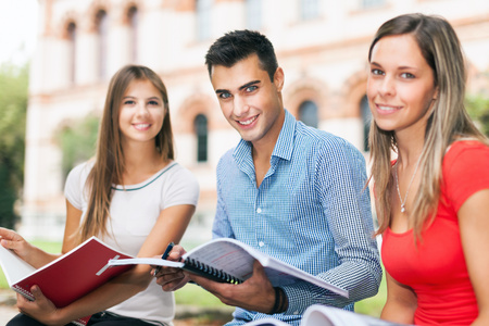 school exam: Outdoor portrait of three smiling students studying in a park