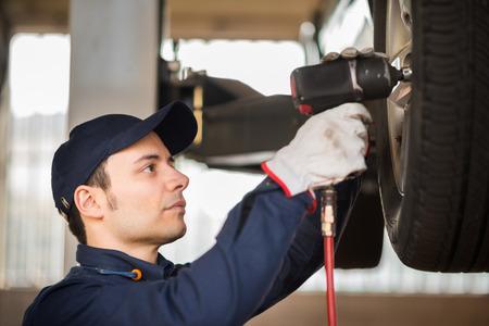auto garage: Portrait of a mechanic replacing a wheel
