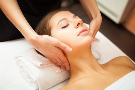 masajes faciales: Mujer hermosa que recibe un masaje Foto de archivo