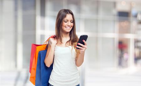 Giovane donna con le borse della spesa e un telefono cellulare