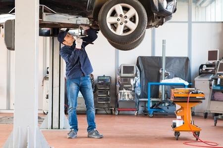 Portrait of a mechanic repairing a car in his garage