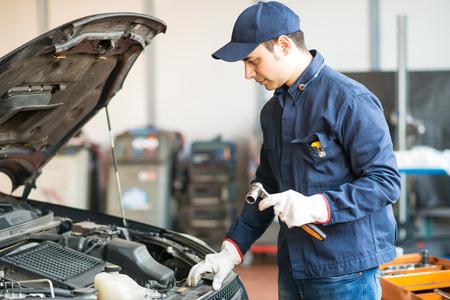 mecanico: Retrato de un mecánico que sostiene una llave en su garaje