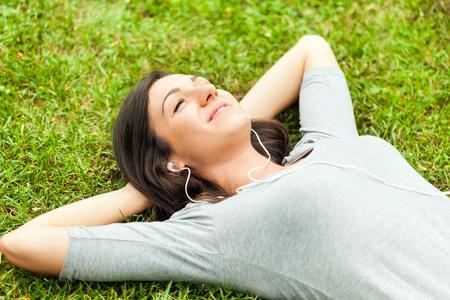 escuchando musica: Mujer que se relaja en la hierba mientras escuchas música