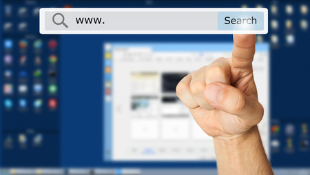 computer button: Hand clicking a search button. Computer monitor in the background Stock Photo