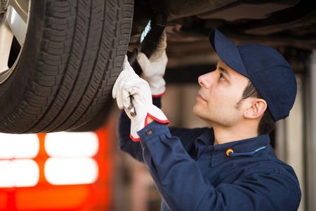 garage mechanic: Mechanic using a lamp to inspect a lifted car