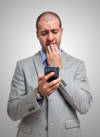 Portrait of a scared man looking at his mobile phone photo