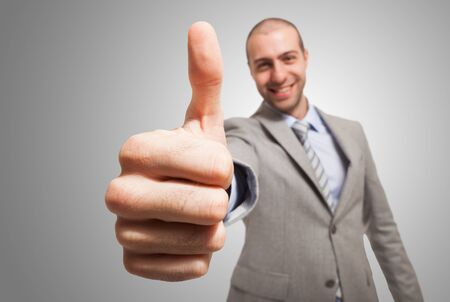 Portrait of a funny businessman giving thumbs up photo