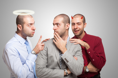the split: Man listening to the angel and devil self to make a choice Stock Photo